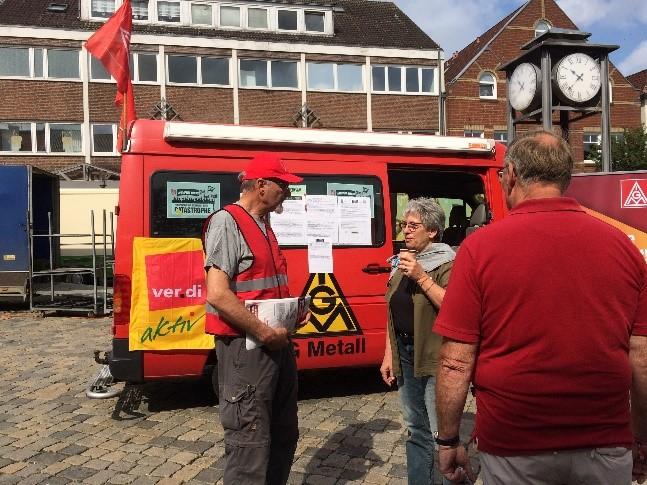 """Im Hintergrund ein roter Transporter angeheftet eine  Fahne """"ver.di aktiv"""", beschriftet mit IGM, Metall, davor eine drei Menschen die reden, einer trägt eine rote Weste, Kappe und hat Flugblätter in der Hand."""